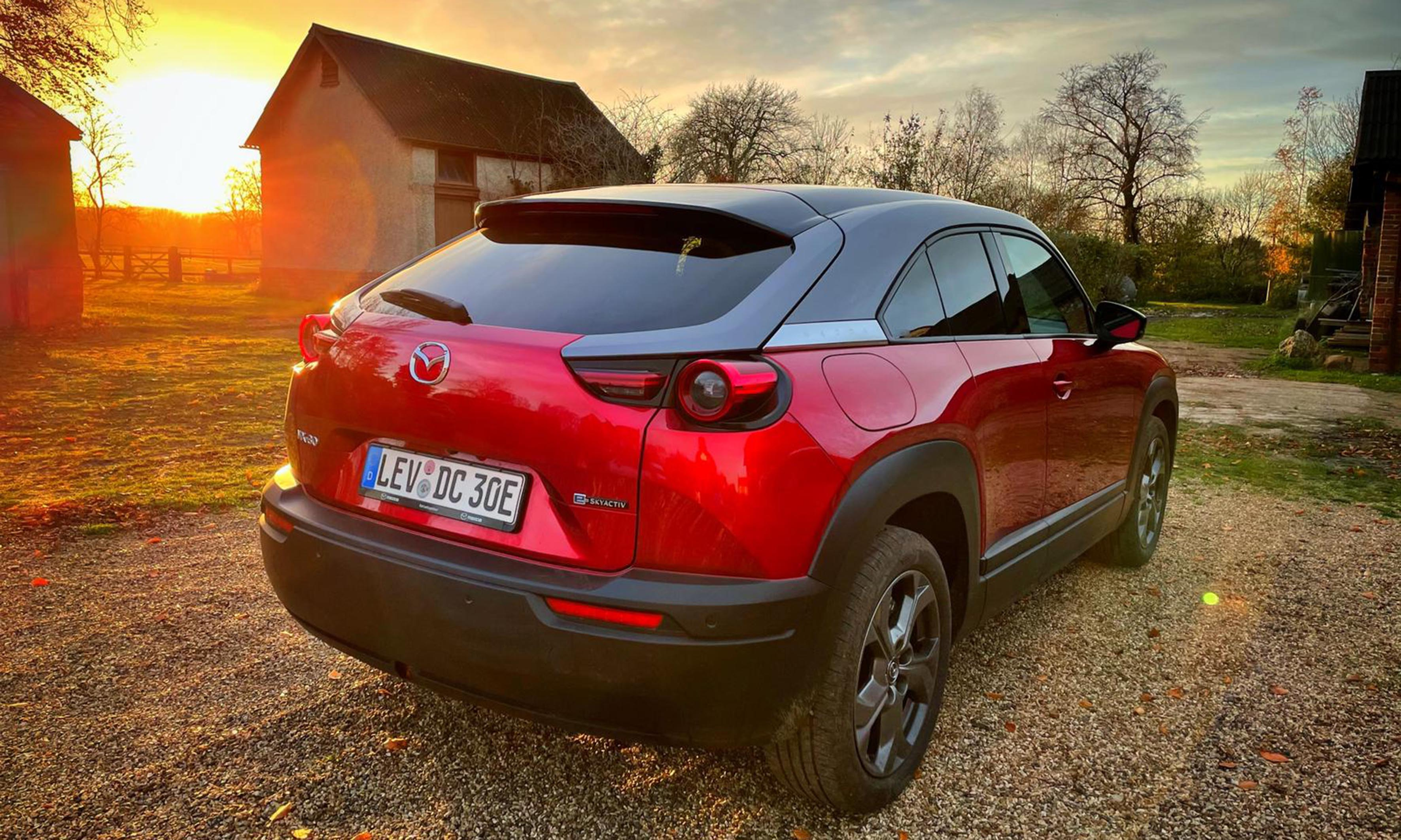 Red Mazda electric car at sunset