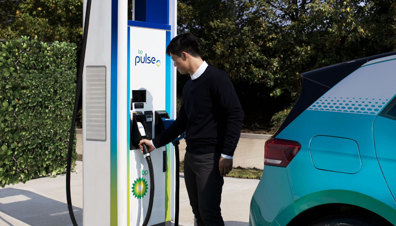 man charging electric car at bp pulse charging point